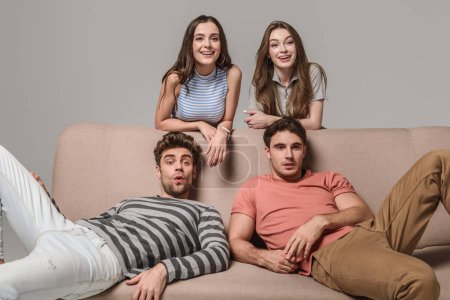 Photo for Happy young friends sitting on sofa isolated on grey - Royalty Free Image