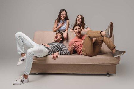 Foto de Amigos felices riendo y relajándose en el sofá en gris - Imagen libre de derechos