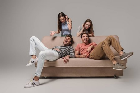 Photo for Young friends laughing and relaxing on sofa on grey - Royalty Free Image