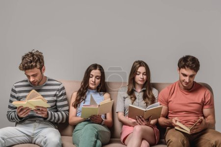Photo for Young bored friends reading books while sitting on sofa on grey - Royalty Free Image