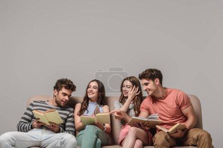 Photo pour Amis souriants parlant et lisant des livres assis sur le canapé sur le gris - image libre de droit