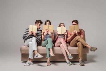 Photo pour Amis tenant des livres assis sur un canapé sur gris - image libre de droit