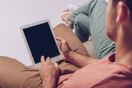 Photo pour Vue en coupe d'un couple utilisant une tablette numérique avec écran vierge ensemble isolé sur gris - image libre de droit