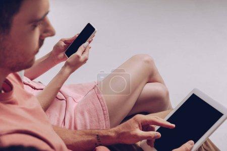 Photo pour Vue recadrée du couple à l'aide d'appareils numériques avec écrans vierges assis ensemble isolé sur gris - image libre de droit