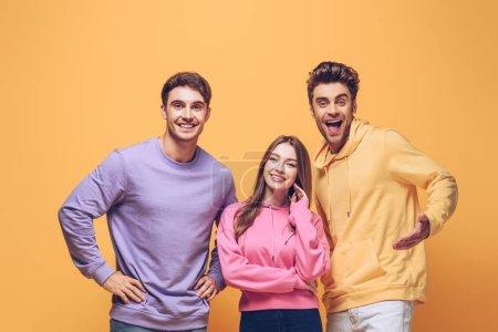 Photo pour Des amis souriants debout ensemble, isolés sur le jaune - image libre de droit