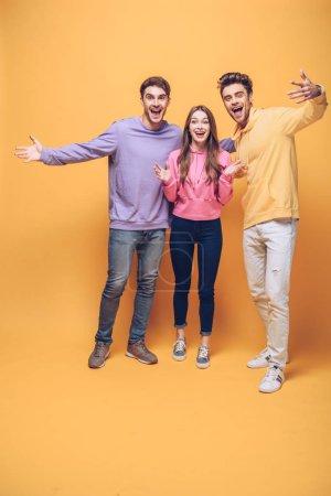 Photo pour Amis affectifs heureux debout ensemble, isolés sur le jaune - image libre de droit