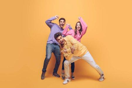 Photo pour Amis excités s'amuser ensemble, sur jaune - image libre de droit