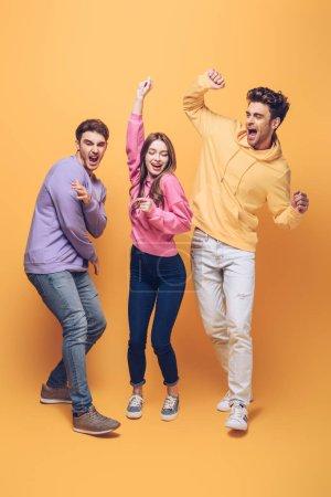 Foto de Amigos jóvenes emocionados divertiéndose juntos, en amarillo - Imagen libre de derechos