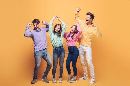 Photo pour De jeunes amis enthousiastes dansant ensemble, en jaune - image libre de droit
