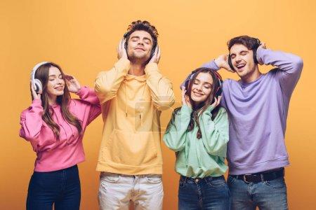Photo pour Des amis joyeux qui écoutent de la musique dans des écouteurs et qui dansent ensemble, isolés sur le jaune - image libre de droit