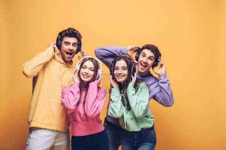 Photo for Happy friends listening music in headphones and dancing together, isolated on yellow - Royalty Free Image