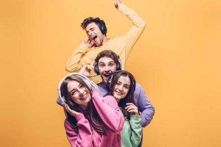 Photo pour Des amis souriants qui écoutent de la musique dans des écouteurs et qui dansent ensemble, isolés en jaune - image libre de droit