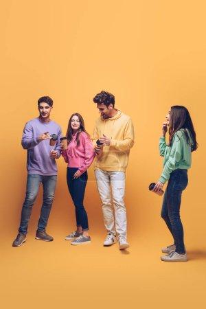 Photo pour Des amis joyeux qui parlent et tiennent du café pour aller, en jaune - image libre de droit