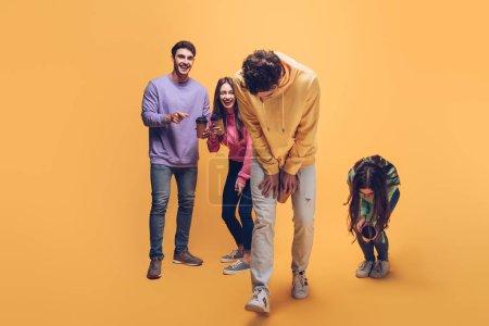 amigos riendo hablando y sosteniendo café para llevar, en amarillo
