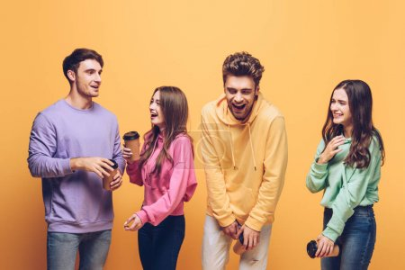 cheerful friends talking and holding coffee to go, isolated on yellow