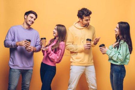 Photo pour Des amis joyeux qui parlent et tiennent le café pour aller, isolés sur le jaune - image libre de droit