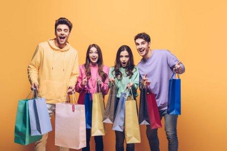 Foto de Amigos apasionados sosteniendo las bolsas de la compra juntas, aislados en amarillo - Imagen libre de derechos