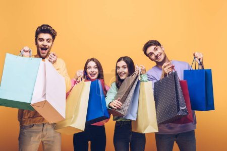 Photo for Happy friends holding shopping bags together, isolated on yellow - Royalty Free Image
