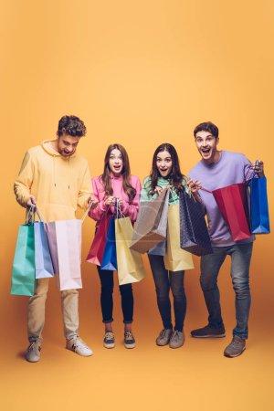 Photo pour Surpris de jeunes amis tenant des sacs à provisions ensemble, en jaune - image libre de droit