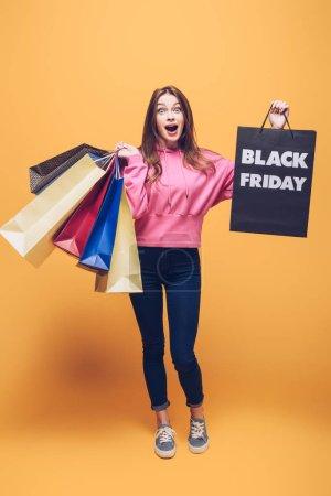 Photo pour Fille excitée tenant des sacs à provisions le vendredi noir, en jaune - image libre de droit
