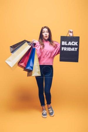Foto de Sorprendida de tener bolsas de la compra el viernes negro, en amarillo. - Imagen libre de derechos