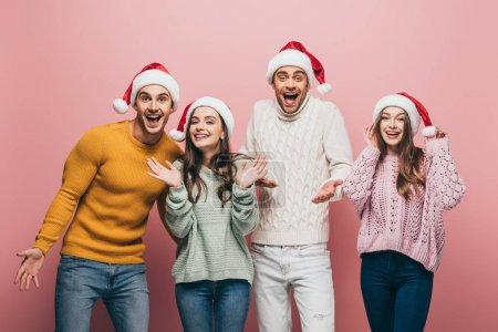 Photo for Excited friends in sweaters and santa hats, isolated on pink - Royalty Free Image