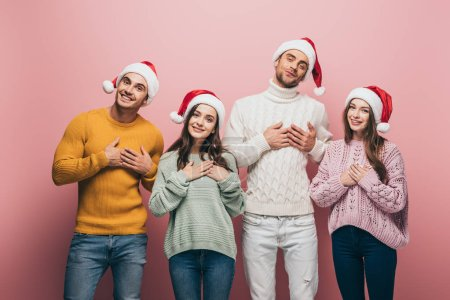 Photo for Happy friends in sweaters and santa hats holding hands on hearts, isolated on pink - Royalty Free Image