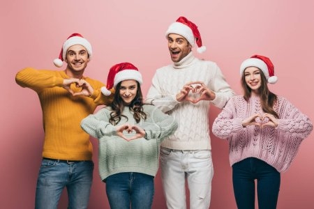 Photo for Happy friends in sweaters and santa hats showing heart symbols, isolated on pink - Royalty Free Image