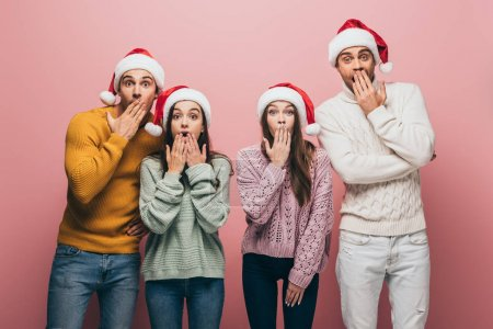 Photo for Shocked friends in sweaters and santa hats, isolated on pink - Royalty Free Image