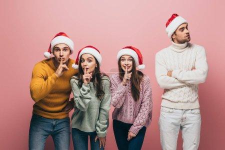 Photo pour Des amis joyeux en chandail et des chapeaux santa montrant des symboles de silence, isolés sur le rose - image libre de droit