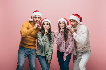 Photo for Happy friends in sweaters and santa hats showing silence symbols, isolated on pink - Royalty Free Image