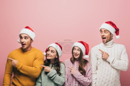 Photo for Happy friends in sweaters and santa hats pointing away, isolated on pink - Royalty Free Image