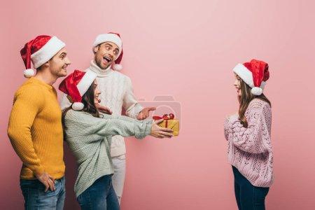 Photo pour Joyeuses amies en santa chapeaux de Noël offerts à la fille, isolés sur rose - image libre de droit