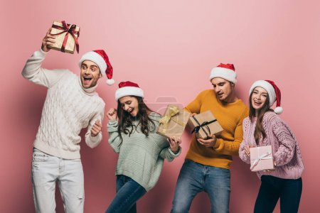 Photo for Happy friends in santa hats dancing and holding christmas presents, isolated on pink - Royalty Free Image