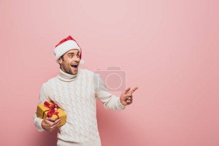 Photo pour Bel homme excité dans santa chapeau pointant et tenant cadeau de Noël, isolé sur rose - image libre de droit
