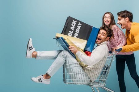 Photo for Excited friends having fun with shopping cart and shopping bags on black friday, isolated on blue - Royalty Free Image