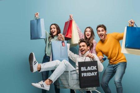 Photo pour De jeunes amis enthousiastes qui s'amusent avec des sacs dans leur chariot le vendredi noir, isolés le dimanche bleu - image libre de droit