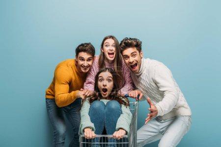 Photo pour Des amis excités et effrayés qui s'amusent avec leur chariot, isolés en bleu - image libre de droit