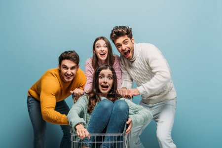 Photo for Frightened friends yelling and having fun with shopping cart, isolated on blue - Royalty Free Image