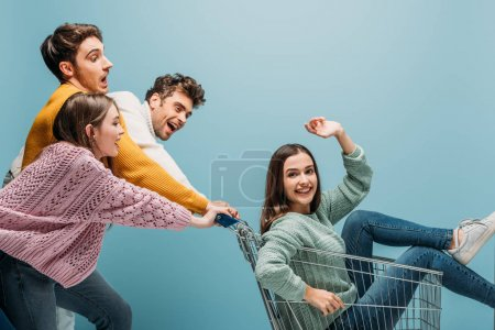 Photo pour Happy friends having fun and riding girl in shopping cart, isolated on blue - image libre de droit