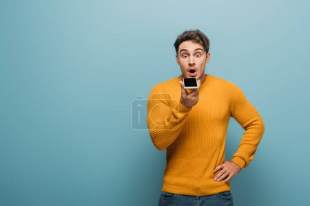shocked handsome man using smartphone, isolated on blue