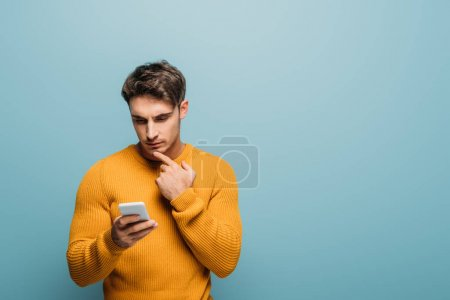 Photo for Handsome thoughtful man using smartphone, isolated on blue - Royalty Free Image
