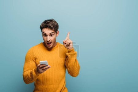 Photo for Surprised man using smartphone and having idea, isolated on blue - Royalty Free Image