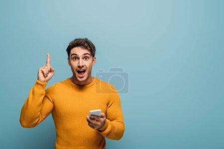 homme surpris en utilisant smartphone et pointant vers le haut, isolé sur bleu