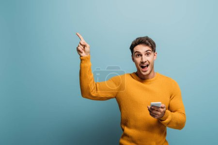 excited handsome man pointing and using smartphone, isolated on blue