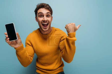 Photo for Excited man gesturing and showing smartphone with blank screen, isolated on blue - Royalty Free Image
