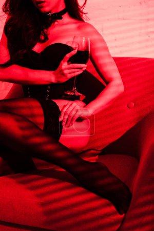 Photo pour Crochet vue d'une femme passionnée en bas assise dans un fauteuil avec un verre de vin à la lumière rouge - image libre de droit