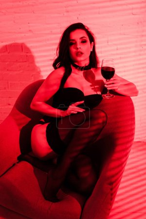 Photo for Beautiful passionate woman sitting in armchair with glass of wine in red light - Royalty Free Image