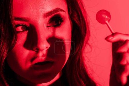 Photo pour Séduisante et passionnée fille mangeant des sucettes en lumière rouge - image libre de droit