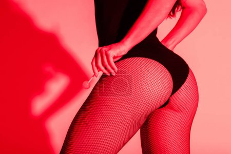 Photo for Cropped view of girl with sexy buttocks in fishnet tights holding lollipop in red light - Royalty Free Image